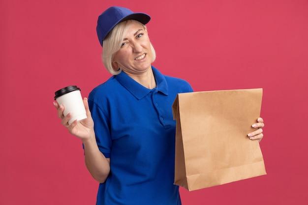 Femme de livraison blonde d'âge moyen mécontente en uniforme bleu et casquette tenant un paquet de papier et une tasse à café en plastique