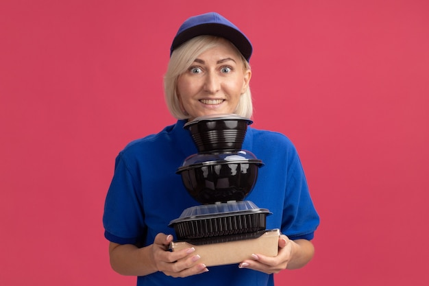 Une femme de livraison blonde d'âge moyen souriante en uniforme bleu et une casquette tenant un emballage de nourriture en papier et des contenants de nourriture mettant le menton dessus