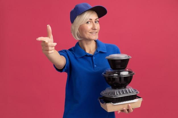 Femme de livraison blonde d'âge moyen souriante en uniforme bleu et casquette tenant un emballage de nourriture en papier et des contenants de nourriture regardant et pointant vers la caméra