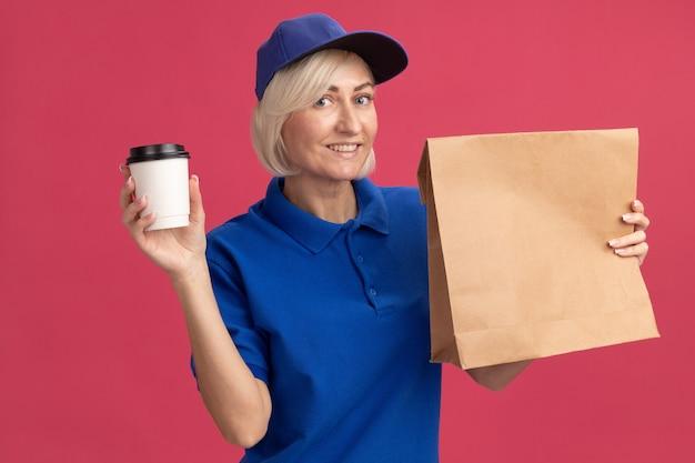 Femme de livraison blonde d'âge moyen souriante en uniforme bleu et casquette tenant un paquet de papier et une tasse à café en plastique