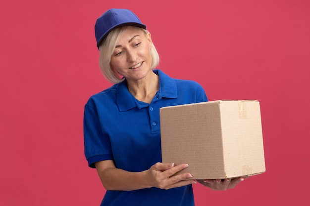 Femme de livraison blonde d'âge moyen souriante en uniforme bleu et casquette tenant et regardant une boîte en carton