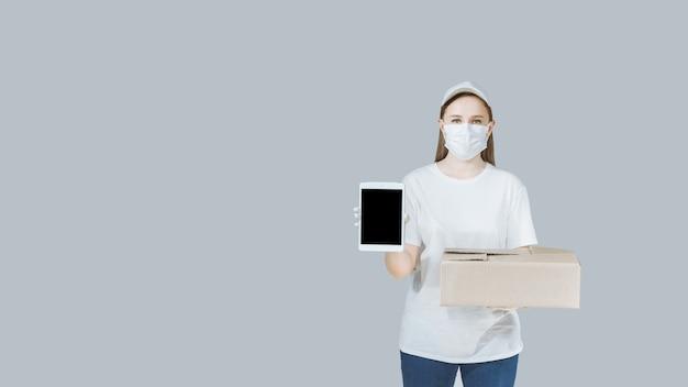 Femme de livraison avec une boîte et une tablette dans les mains dans un masque et des gants dans un uniforme blanc