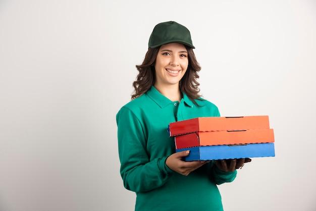 Femme de livraison avec des boîtes à pizza posant sur blanc.