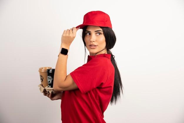 Femme de livraison avec des cafés tenant sa casquette. photo de haute qualité