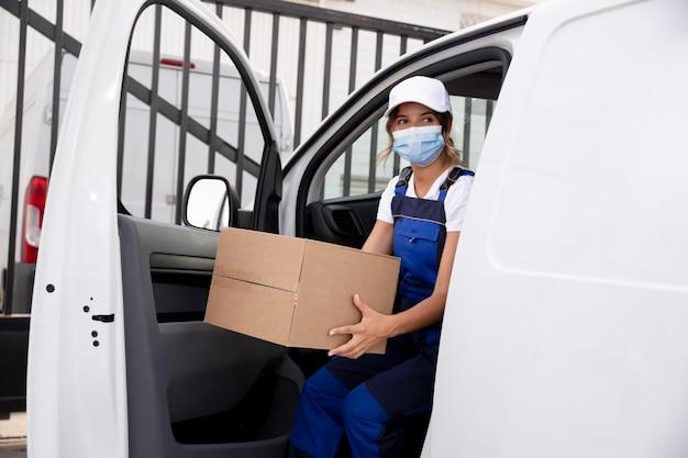Femme de livraison de coup moyen portant un masque