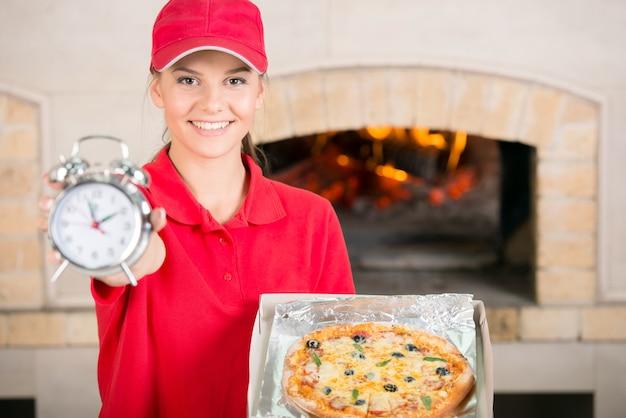 Femme de livraison avec une délicieuse pizza dans une boîte à pizza et une horloge.