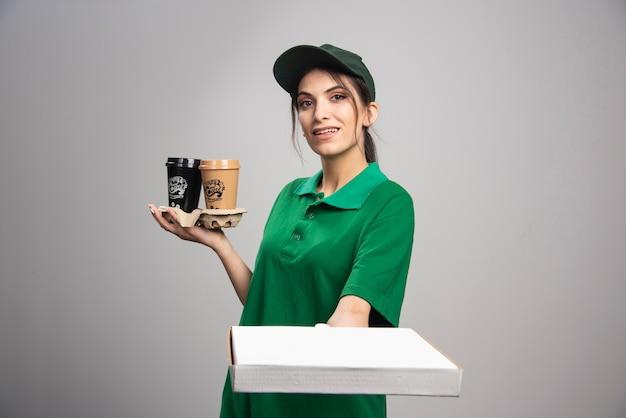 Femme de livraison donnant une boîte à pizza au client
