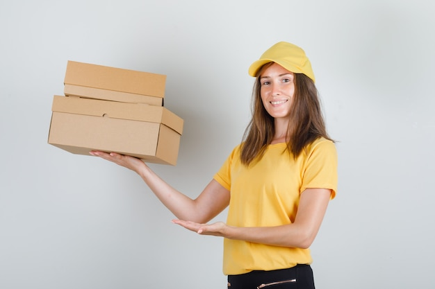 Femme de livraison montrant des boîtes en carton en t-shirt jaune, pantalon, casquette et à la joie.