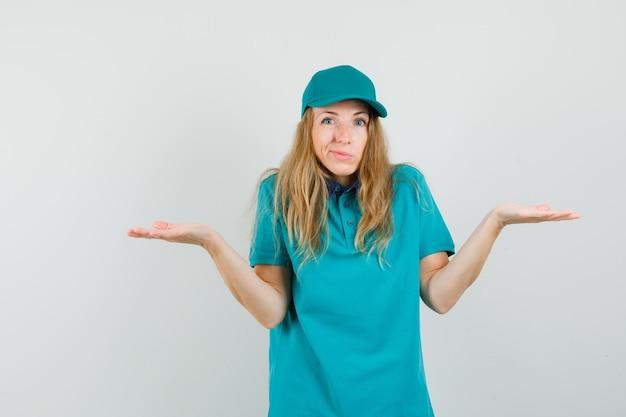 Femme de livraison montrant un geste impuissant en haussant les épaules en t-shirt, casquette et à la confusion