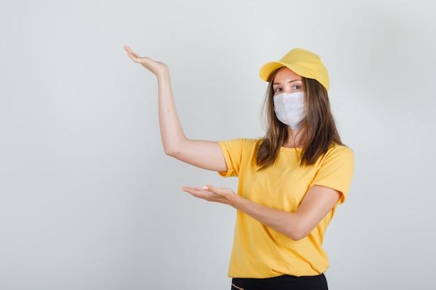 Femme de livraison montrant quelque chose avec les mains en t-shirt, pantalon, casquette et masque et à la joie