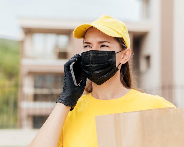 Femme de livraison parlant au téléphone gros plan