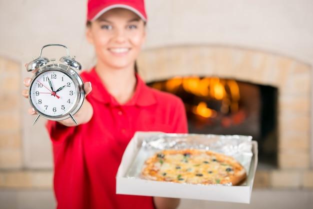 Femme de livraison avec une pizza délicieuse dans une boîte à pizza.