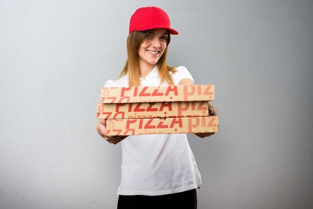 Femme de livraison de pizza heureux sur fond texturé