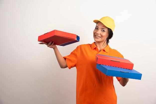 Femme de livraison de pizza tenant un tas de pizzas sur un mur blanc.