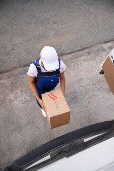 Femme de livraison de plein coup tenant la boîte