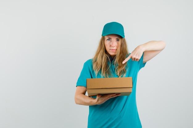 Femme de livraison pointant sur une boîte en carton en t-shirt, casquette