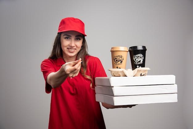 Femme de livraison positive tenant une pizza et des tasses à café sur un mur gris.
