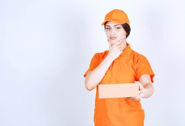 Femme de livraison réfléchie sur mur blanc