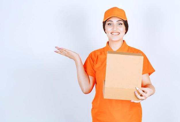 Femme de livraison souriante tenant une boîte ouverte