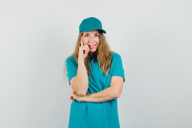 Femme de livraison en t-shirt, casquette debout dans la pensée pose et à la joie
