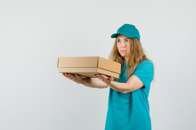 Femme de livraison en t-shirt, casquette livrant une boîte en carton