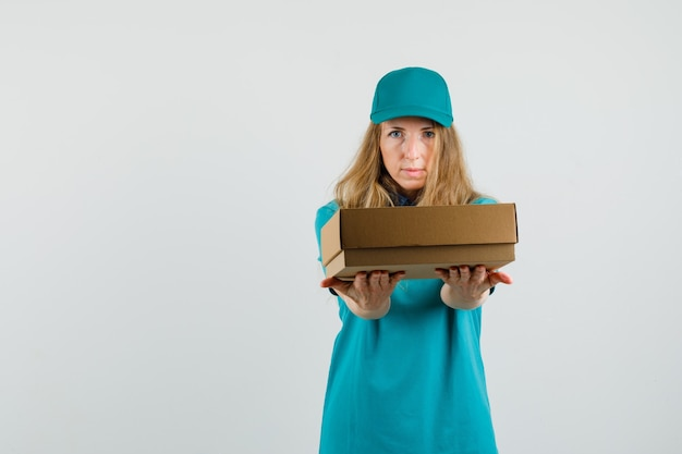 Femme de livraison en t-shirt, casquette présentant une boîte en carton