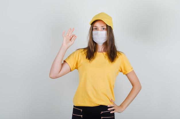 Femme de livraison en t-shirt, pantalon, casquette, masque montrant le geste ok et à la joie