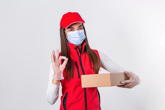 Femme de livraison tenant des boîtes en carton dans des gants en caoutchouc et un masque médical. copie espace.