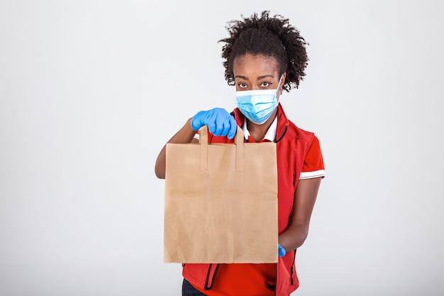 Femme de livraison tenant un sac en papier dans des gants en caoutchouc médical et maskshowing thumb up. copie espace. transport de livraison rapide et gratuit