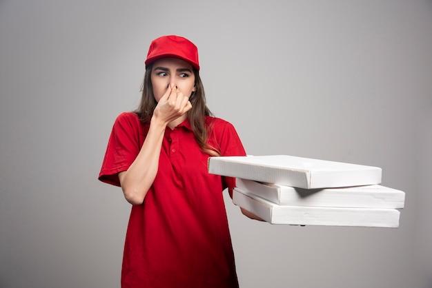 Femme de livraison tenant son nez fermement tout en portant des boîtes de pizza.