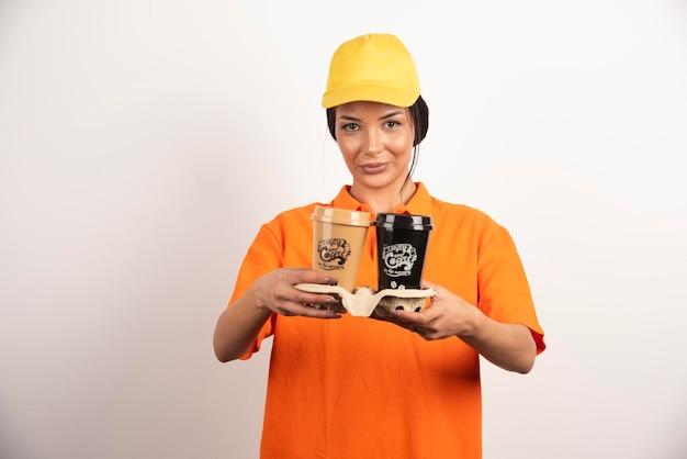 Femme de livraison tenant des tasses à café sur un mur blanc.