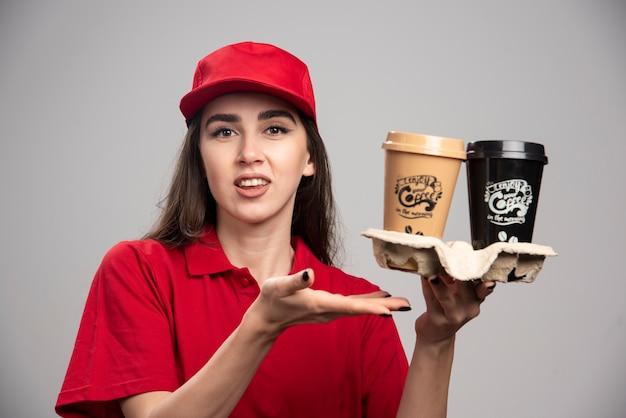 Femme de livraison tenant des tasses à café sur un mur gris.