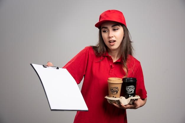 Femme de livraison tenant des tasses à café et regardant le presse-papiers.