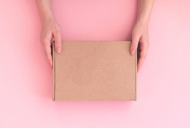 Une femme de livraison tient une boîte à colis avec un espace de copie sur fond rose, une maquette ou un modèle de boîte en carton
