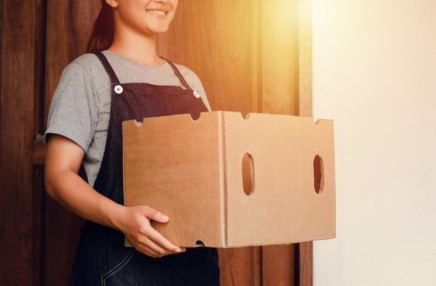 Femme de livraison transportant des boîtes de colis aux clients idée d'entreprise de livraison. bon sourire. bon service.