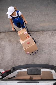 Femme de livraison transportant des boîtes plein coup