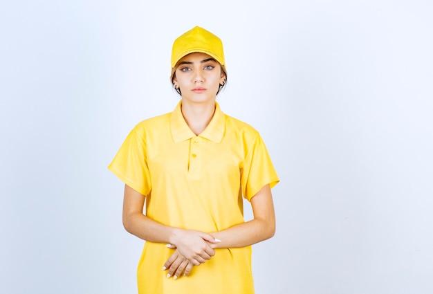 Femme de livraison en uniforme jaune debout et regardant la caméra.