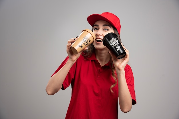 Femme de livraison en uniforme rouge, boire du café.
