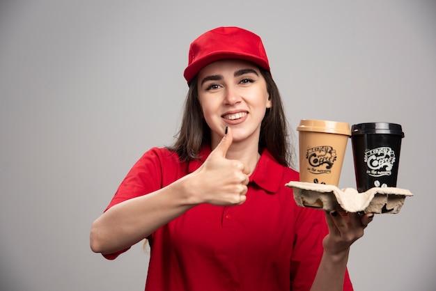 Femme de livraison en uniforme rouge tenant des tasses à café et faisant les pouces vers le haut.