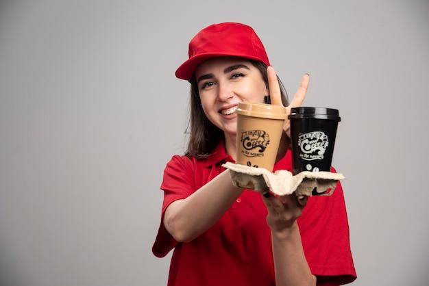 Femme de livraison en uniforme rouge tenant des tasses à café.
