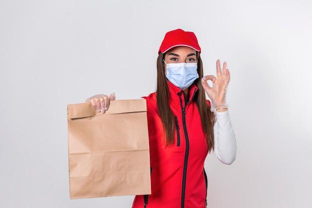 Femme de livraison en uniforme rouge tenir le paquet de papier craft avec de la nourriture isolé sur fond blanc