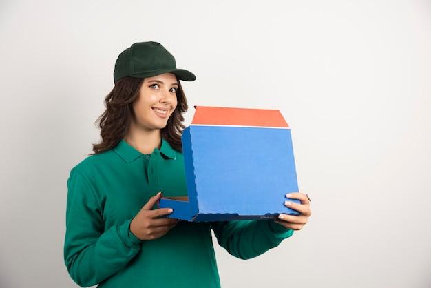Femme de livraison en uniforme vert tenant une boîte à pizza ouverte.