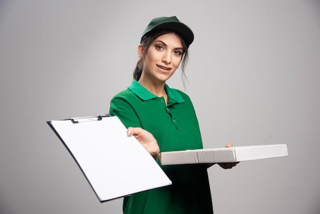 Femme de livraison en vert montrant le presse-papiers sur fond gris.