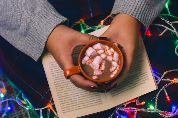 Femme avec livre et boisson chaude dans les mains vue de dessus, vacances d'hiver agréables