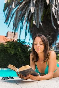 Femme, livre lecture, mensonge, sur, bord piscine