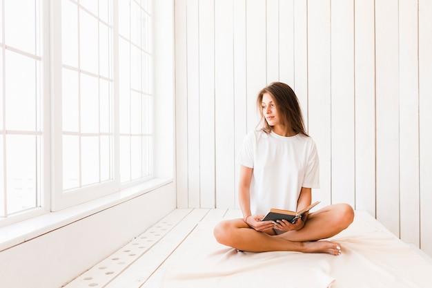 Femme avec un livre ouvert en détournant les yeux
