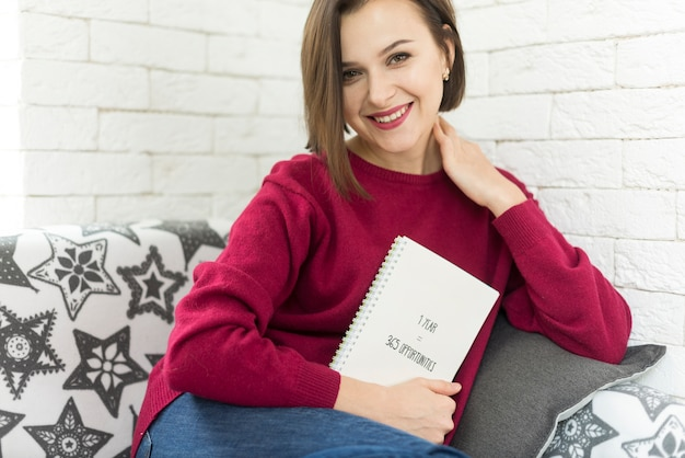 Femme avec un livre regardant camara