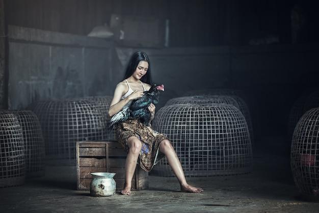 Femme locale thaïlandaise avec coq