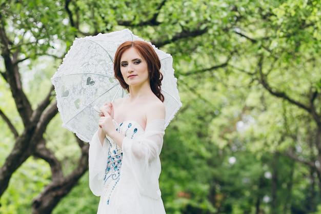 Femme en longue robe blanche dans le jardin d'été