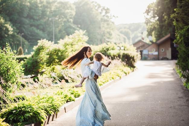 Femme en longue robe bleue tourbillonne avec sa petite fille sur le chemin de la chaussée